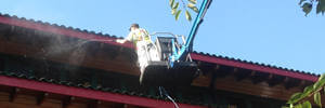 Man on crane cleaning roof