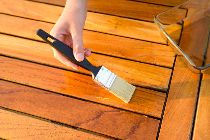 Hand holding a brush applying varnish paint on a wooden garden table